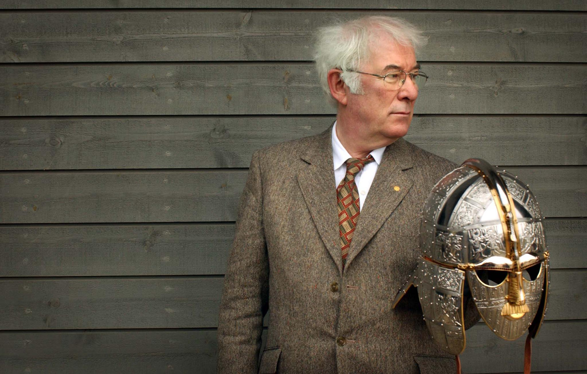 Mandatory Credit: Photo by REX/Tom Pilston / The Independent (2448851a) SEAMUS HEANEY AUTHOR OF THE ACCLAIMED TRANSLATION OF BEOWULF HOLDS A REPLICA OF THE SUTTON HOO HELMET AT THE OPENING OF A NEW EXHIBITION CENTRE AT THE SUTTON HOO SITE WHICH INCLUDES TREASURES LENT BY THE BRITISH MUSEUM. 13/3/02 SEAMUS HEANEY AUTHOR OF THE ACCLAIMED TRANSLATION OF BEOWULF HOLDS A REPLICA OF THE SUTTON HOO HELMET AT THE OPENING OF A NEW EXHIBITION CENTRE AT THE SUTTON HOO SITE WHICH INCLUDES TREASURES LENT BY THE BRITISH MUSEUM. 13/3/02